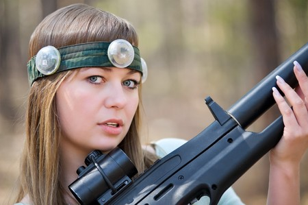 a young caucasian woman with a gun for a laser war game photo