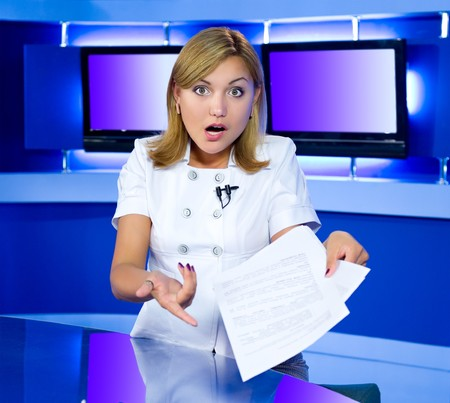 newsreader: a television anchorwoman at a studio is shocked by news she has in her hands Stock Photo