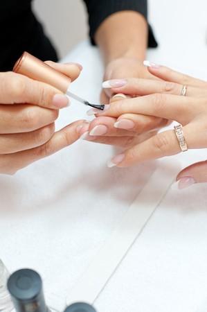 enamel: manicure making - female hands, covering of transparent enamel