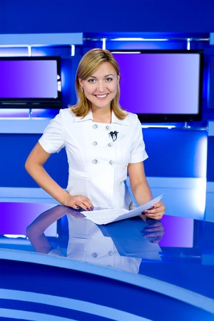 newsreader: a television anchorwoman at studio, looks into camera
