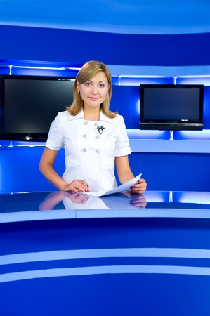 newsreader: a television anchorwoman at studio, looks into camera