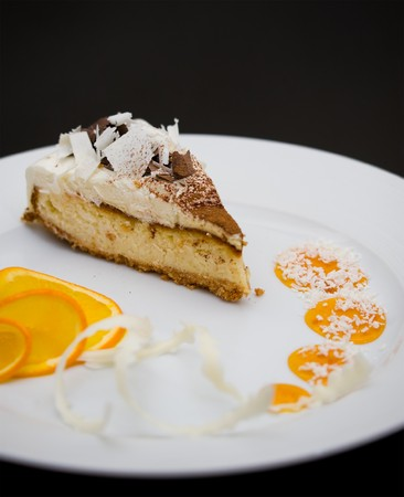 a piece of sponge cake with white and dark chocolate, served with orange slices and syrup photo