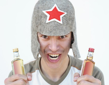 a young man in a Budenny cap holds alcohol drinks in both hands photo