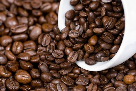 roasted coffee beans and a cup on them photo
