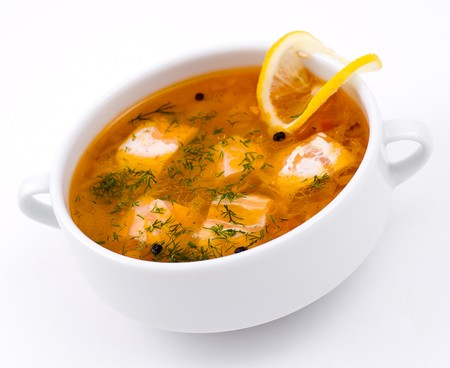 rich soup with salmon, served with lemon photo