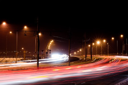 statics: night city traffic lights in motion under street lamps Stock Photo