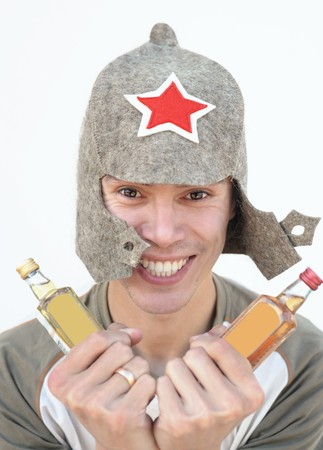 a young man in a Budenny cap holds alcohol drinks in both hands Stock Photo - 8121730