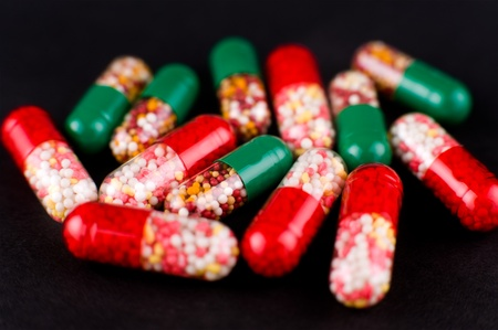 a macro shot of medicines, red and green capsules photo