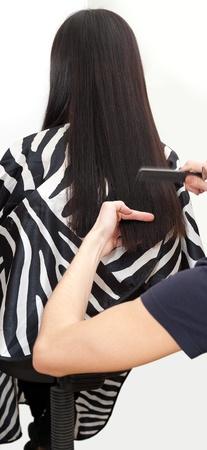 peluqueria: manos masculinas cortan el pelo largo de Morena