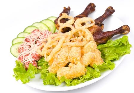 squid rings fried in batter, meat and cheese balls, cheese sticks and grilled chicken legs photo