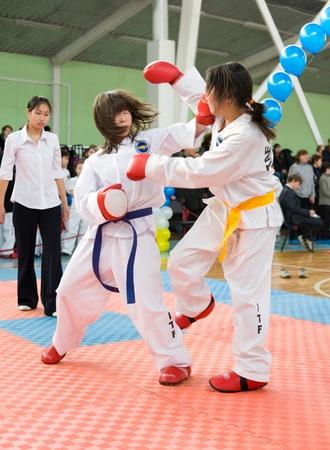 ULAN-UDE, RUSSIA - FEBRUARY 7: Two asian wrestler girls fight at a taekwondo competition on February, 7, 2010 in Ulan-Ude, Buryatia, Russia.