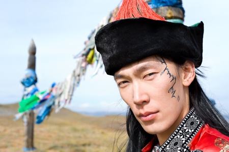 young asian man in national Mongolian suit, his name Chinghis is painted in ancient Mongolian on his face