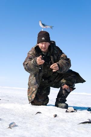 UST-BARGUZIN, RUSSIA - APRIL 11: A fisher throws fish, just caught, at the 5th Annual Baikal Fishing, April 11, 2009 in Ust-Barguzin, Buryatia, Russia. Stock Photo - 8449326