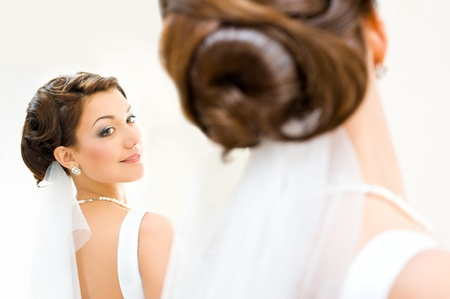 primp: giovane sposa si guarda allo specchio Archivio Fotografico