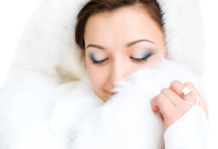 young brunette woman in white fur hood smiles looking down photo