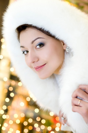 young brunette woman in white fur hood against sparkling background photo