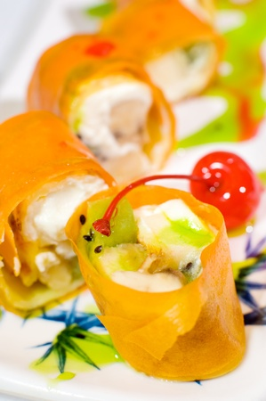 food stuff: sweet sushi rolls with fruits, wrapped into rice paper, macro