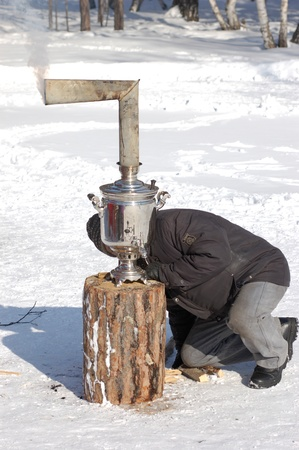 ULAN-UDE, RUSSIA - FEBRUARY 28: A man kindles a classic old samovar on the last day of  Pancake festival, when people eat pancakes with hot tea, February, 28, 2009, Ulan-Ude, Russia. Stock Photo - 8526442