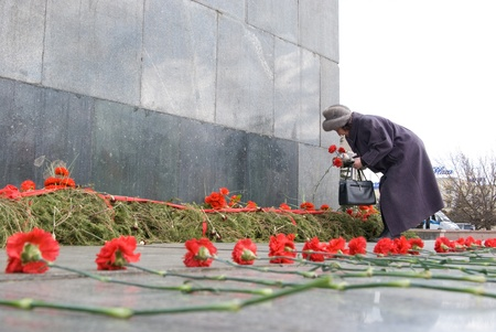 ULAN-UDE, RUSSIA - MAY 1: An elderly woman lays pinks to Lenin's monument at the central city square, May, 1, 2009 in Ulan-Ude, Buryatia, Russia. Stock Photo - 8526445