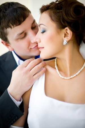 tenderly: a bridegroom embraces tenderly his bride, on their wedding day Stock Photo