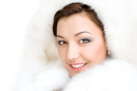 young smiling brunette woman in white fur hood photo