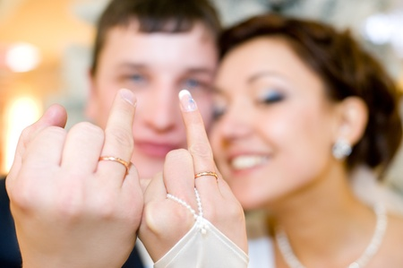 young happy newlyweds show their rings to camera