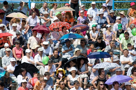 naadan: ULAN-UDE, RUSSIA - JULY 17: The 4th General Session of the World Mongolians Convention, July 17, 2010 in Ulan-Ude, Buryatia, Russia. Spectators suffer from heat saving themselves with umbrellas.