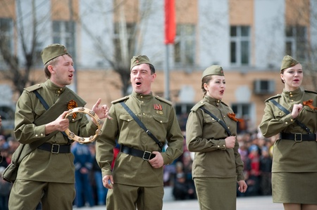 ULAN-UDE, RUSSIA - MAY 9: A group of actors wearing vintage (WWII's period) uniforms perform at the main city squre on annual Victory Day, May, 9, 2009 in Ulan-Ude, Buryatia, Russia. Stock Photo - 8717562