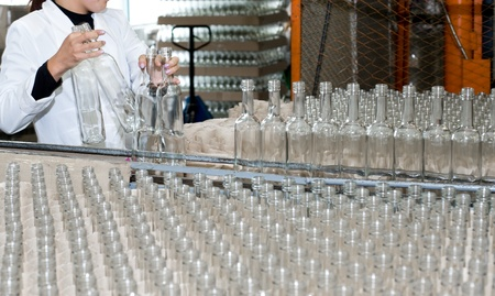 production of alcohol drinks - an operator puts empty bottles on conveyor photo