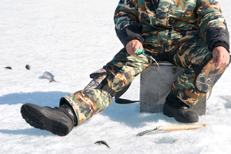 a fisher fishes from an ice hole photo