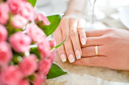 hands of a bride and a bridegroom, just married, a bridal bouquet is beside photo