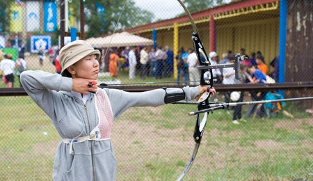 naadan: ULAN-UDE, RUSSIA - JULY 16: A Buryat woman archer coaches for the Surharbaan (annual summer games) competition at a stadium, July 16, 2010 in Ulan-Ude, Buryatia, Russia.