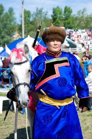 naadan: ULAN-UDE, RUSSIA - JULY 17: The 4th General Session of the World Mongolians Convention, July 17, 2010 in Ulan-Ude, Buryatia, Russia. A Buryat (Mongolian) man stands by his horse.