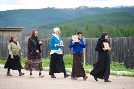 ministration: BATURINO, RUSSIA - JUNE 18: Nuns of the Baturinsky Orthodox Convent make an afternoon icon-bearing procession, June 18, 2010 in Baturino, Buryatia, Russia.