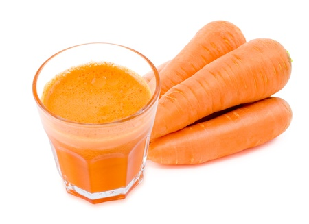 fresh carrot juice in a glass, some carrots, over white