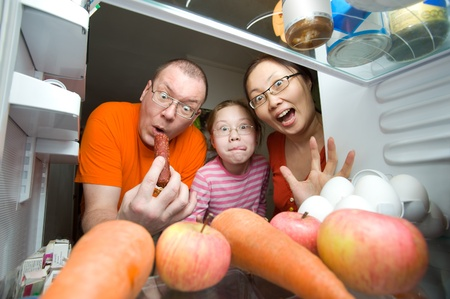 a man, a woman and a girl look into a fridge, with crazy and hungry faces photo