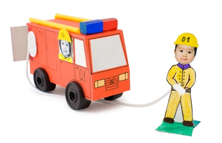 cardboard handicraft - a fireman with a fire engine, my daughter's work, over white photo