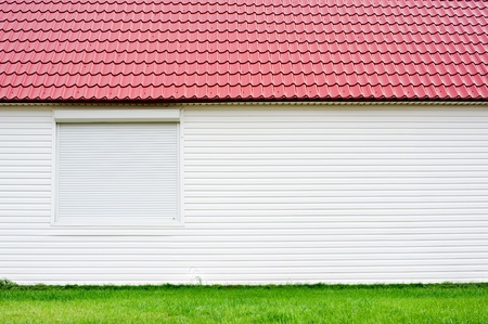 louver boards: a wall of a white house with a red roof on green grass