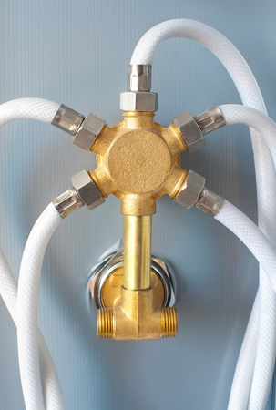 shower cubicle: a splitter for water supply at the back of a shower cubicle