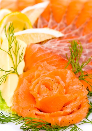 shallow depth of field: sliced smoked salmon served with lemon and salmon rose