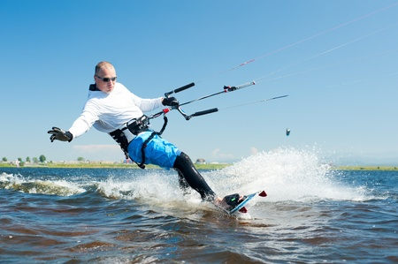 a kitesurfer moves on water on a sunny summer day