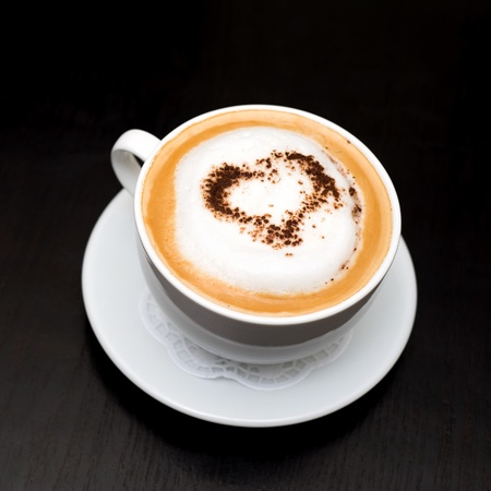 capuccino: cup of cappuccino coffee on saucer, chocolate heart on top, copy space Stock Photo