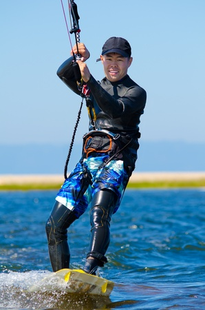 a kitesurfer moves on water on a sunny summer day photo