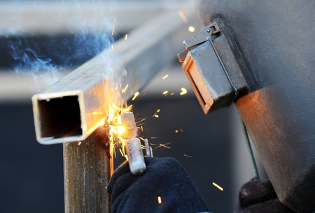 welds: a welder in a safety mask welds