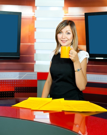 gravida: a pregnant television anchorwoman holds a cup with tea (coffee) Stock Photo
