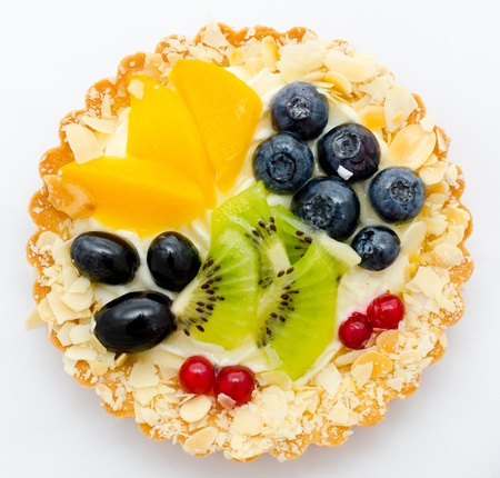 cream on a tartlet served with peach, kiwi and berries