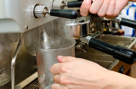 boiling: hands pour boiling water into a measuring jar out of a coffee machine