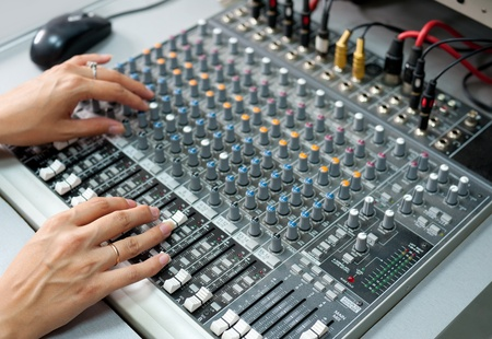 female hands at a sound mixing console photo