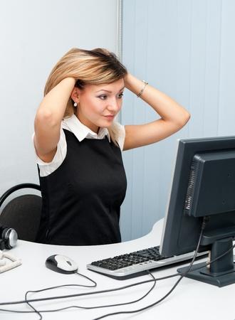 administracion de empresas: una mujer joven se sienta delante de un ordenador perplejo y disgustado