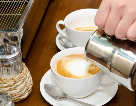 making coffee: a cup of cappuccino coffee is being filled with cream